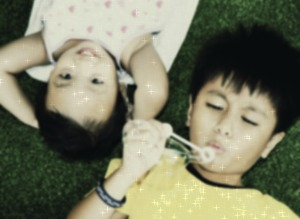 Two Kids Outside Lying And Playing On The Grass